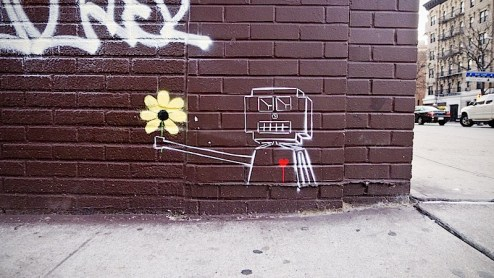 a robot with a flower street art piece in the east village of nyc
