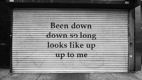been down so long graffiti on a store shutter on bowery in nyc