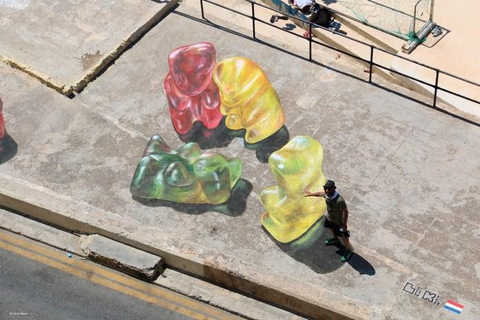 3d street art by Leon Keer at Malta Streetart Festival. Gummy bears gather around 3