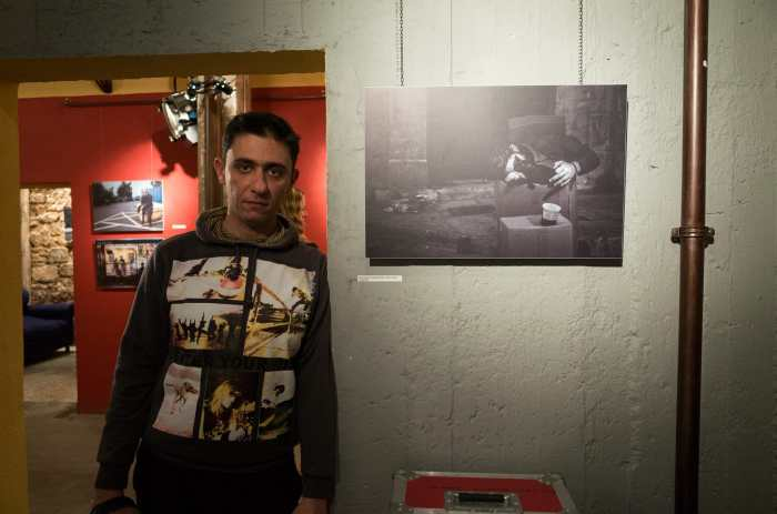 """Gregory Antikian posing next to his photograph """"Best Friends"""""""