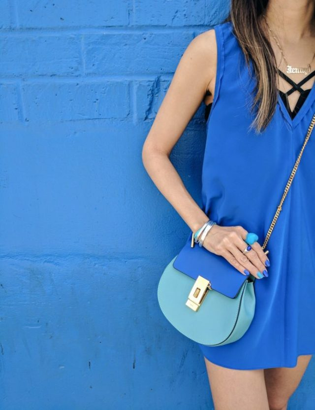 girl with blue chloe drew bag in front of blue wall