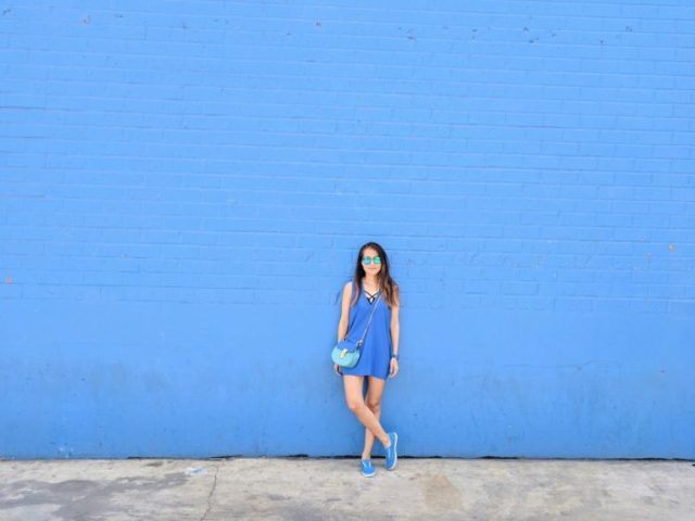 girl in blue standing in front of blue wall