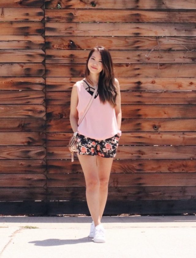 girl in floral shorts standing in front of wood wall