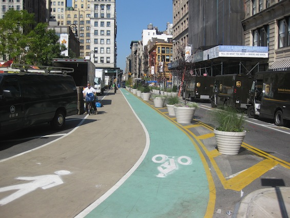 Just north of Union Square on 17th Street is a new protected contraflow bike lane and pedestrian lane. Greenmarket trucks are parked immediately curbside. Photo: Noah Kazis