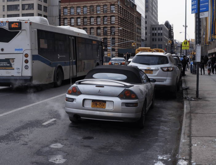 In addition to longer-term design changes, improving Jay Street could start with better enforcement against illegal parking in bus stops and bike lanes. Photo: Street Plans Collaborative