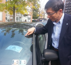 Wellington Chen of the Chinatown Partnership LDC points to a placard parker who left his car on the street all day. Photo: Stephen Miller