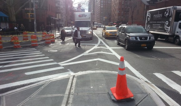 Most of the intersection of Houston Street and Sixth Avenue used to be wide-open asphalt. DOT is now putting the finishing touches on expanded pedestrian space at this deadly crossing. Photo: Stephen Miller