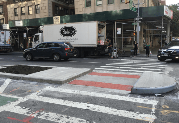 Pedestrian islands, like this one at 73rd Street and Amsterdam Avenue, shorten crossing distances while providing additional protection for cyclists. Image: Robert Baron
