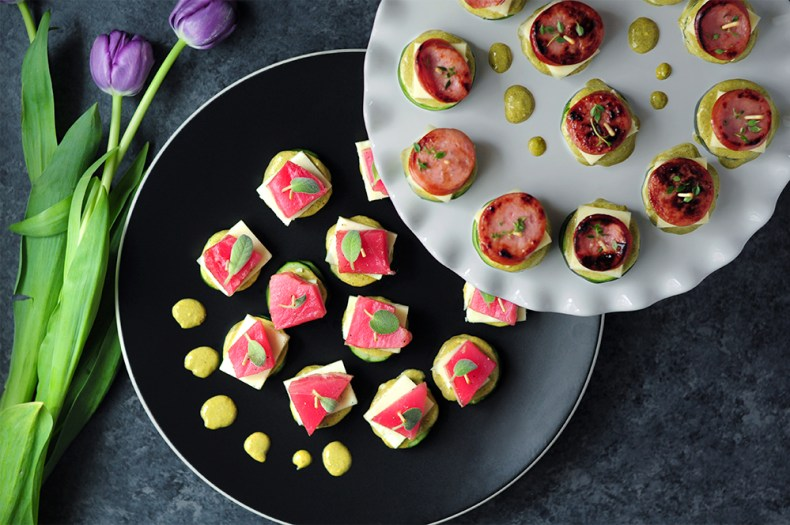 Stackers two ways! On one platter, we've got cucumber stackers with mayo and pesto, Monterey Jack cheese, and topped with seared tuna, then garnished with fresh sage leaves. On the other platter, the zucchini stackers are built with the same sauce and cheese but with kielbasa sausage and oregano on top. These are great appetizer options for your holiday table!