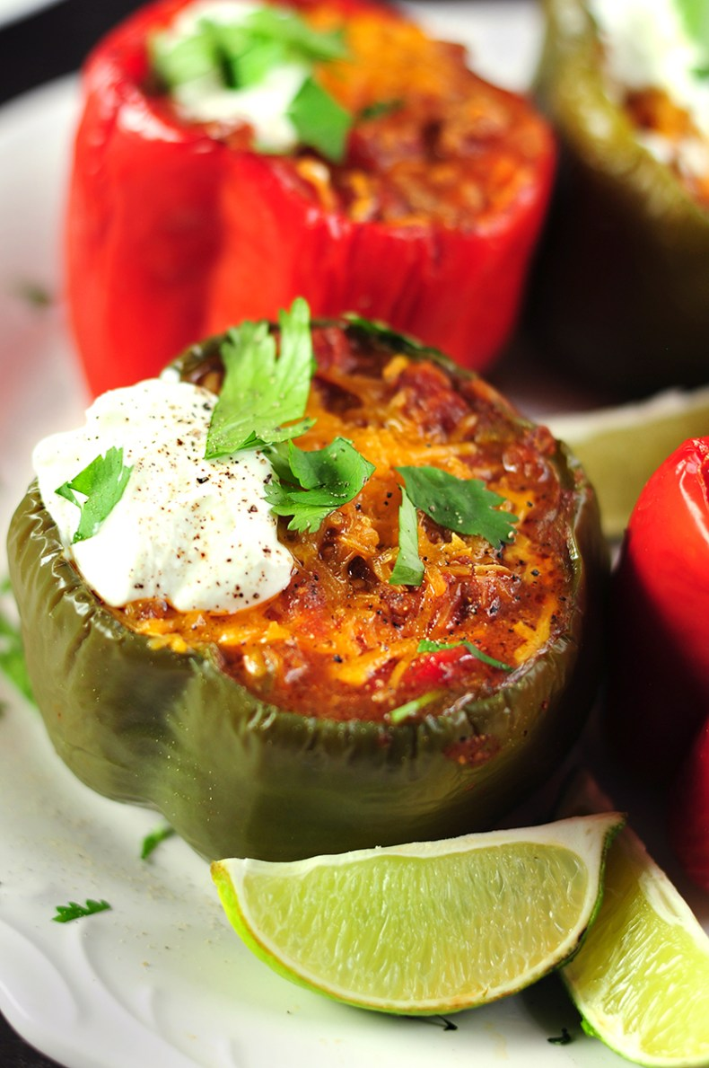 Stuffed peppers with taco-flavored ground beef, onion, tomatoes and cheddar cheese topped with avocado slices, fresh cilantro, and sour cream.