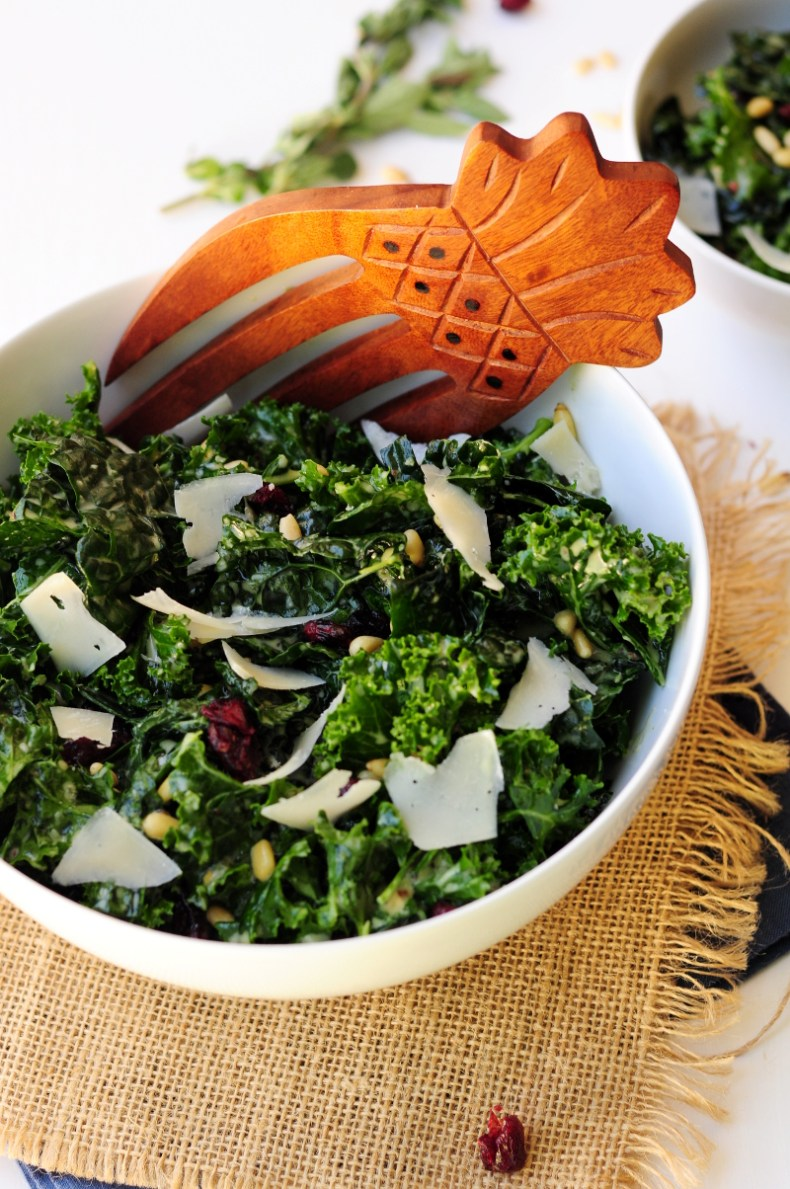 Massaged kale salad tossed with pine nuts and dried cranberries in a delightful oregano lemon salad dressing and topped with shaved Parmesan cheese.