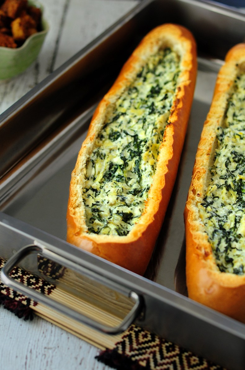 Creamy and cheesy spinach artichoke dip baked in bread boats! These two loaves of stuffed bread are served with freshly baked croutons in one fell swoop. No waste of food, no waste of energy.