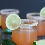 Close-up of three Spicy Guava Margaritas on a black background with fresh limes and jalapeños | StrictlyDelicious.com