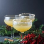 Three winter margaritas with evergreen branches on a black background