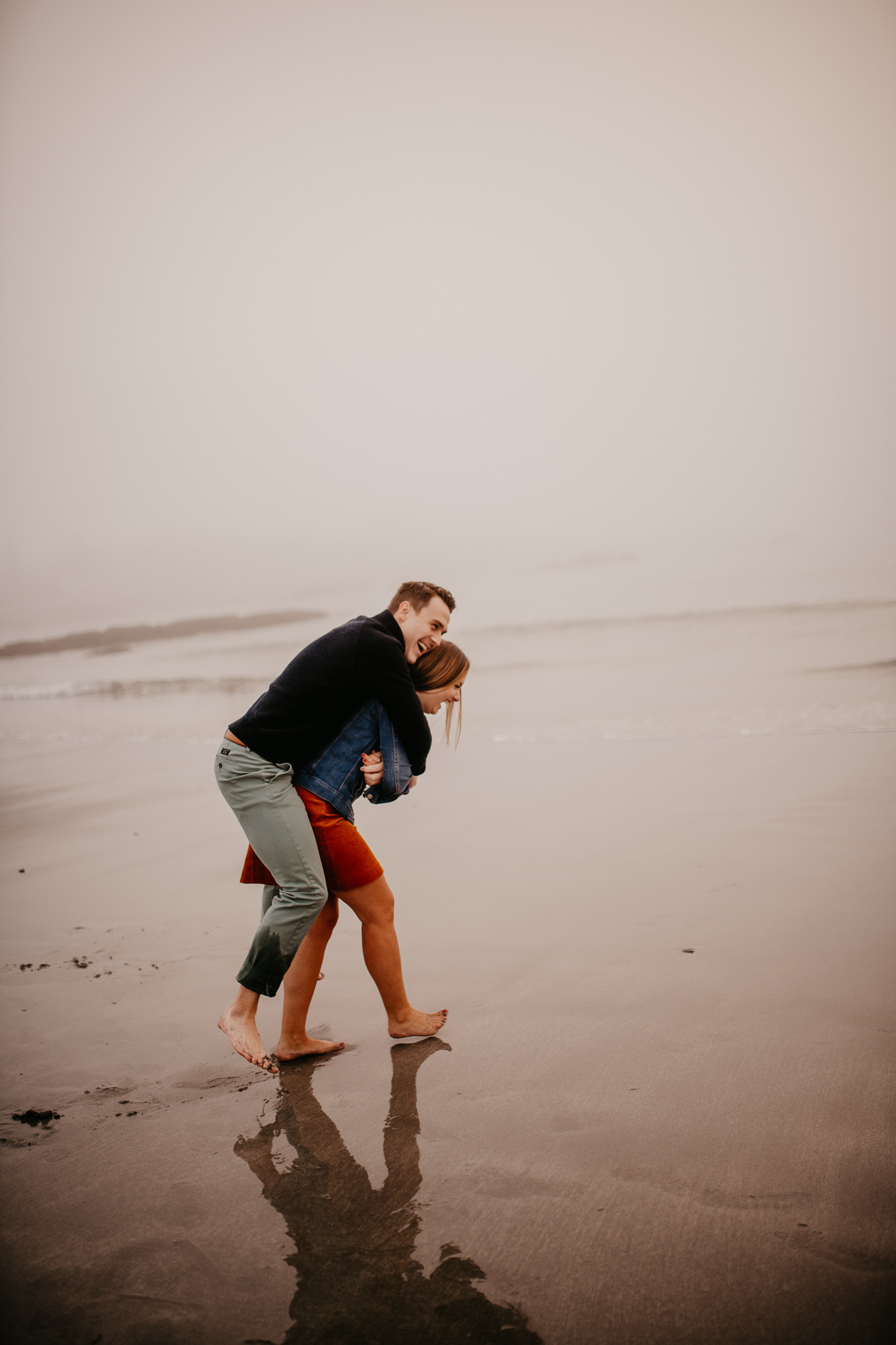 Playful couple on the beach. Maine engagement photos. Beach engagement photos. Preppy engagement photos.