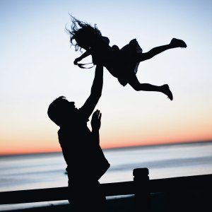 A father throwing his daughter into the air