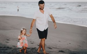 A father leading his daughter by the hand along the beach