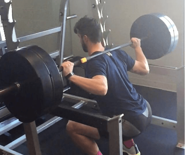 Man squats with a bar-speed tracker on the barbell.