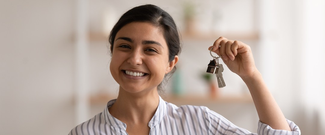 young homeowner proudly holds keys to new home