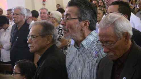 Oscar López (izquierda con camisa negra) y Don Heriberto Marín (a la derecha con camisa negra) quien luchó en el levantamiento del 1950, escuchan palabras del obispo de Mayagüez.