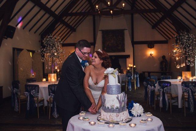 cutting the wedding cake laughing