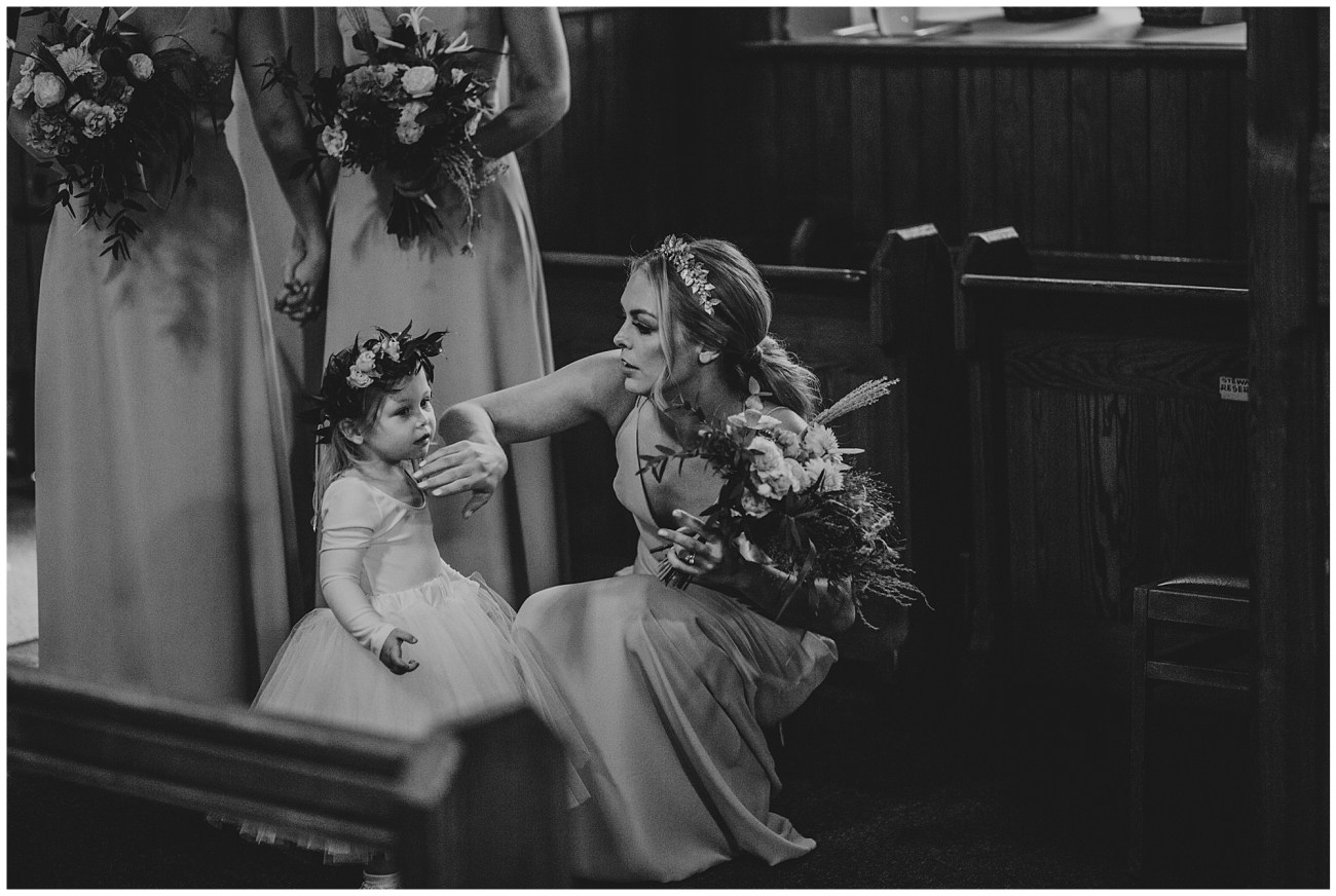 bridesmaid fixing flower girl