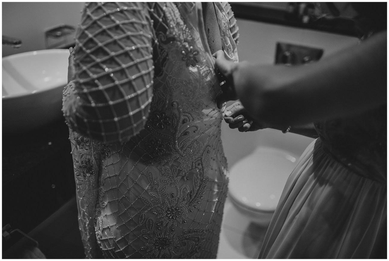 zipping up brides dress