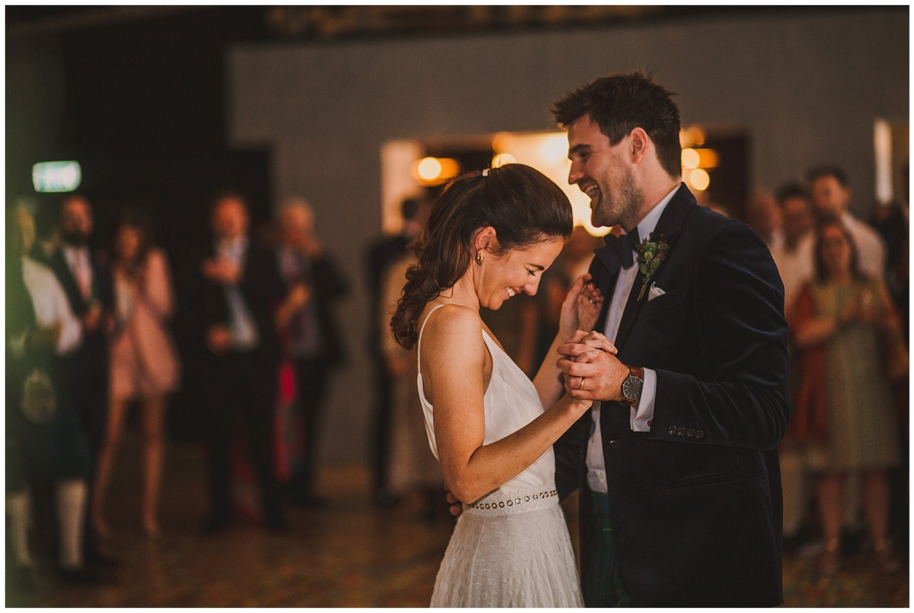 bride and groom laughing whilst dancing