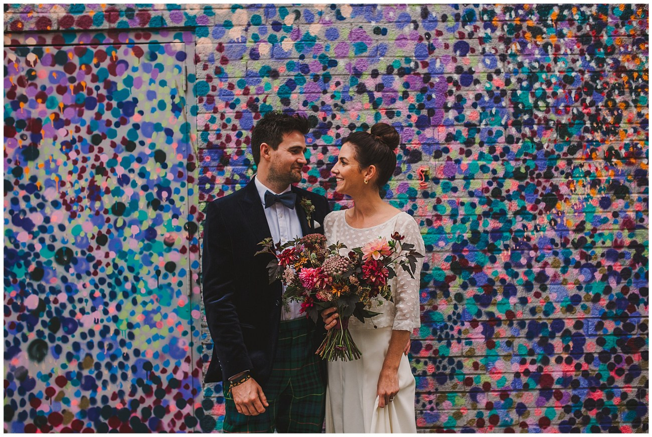 bride and groom with street art