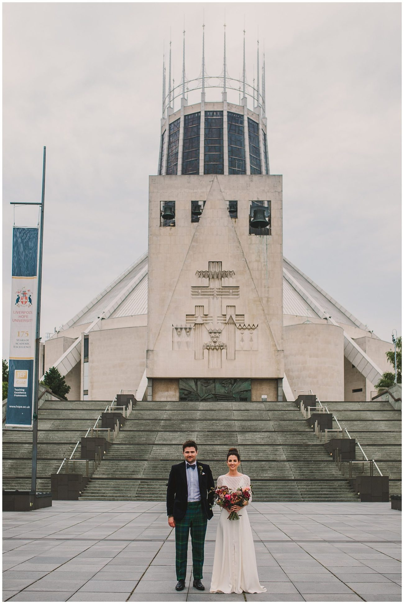 bride and groom in front of metropolitan cathedral liverpool