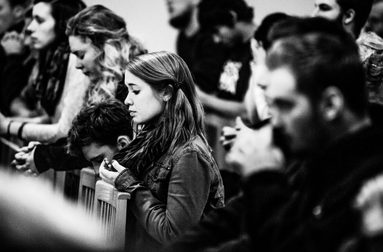Student Amy Johnson kneels during the service.