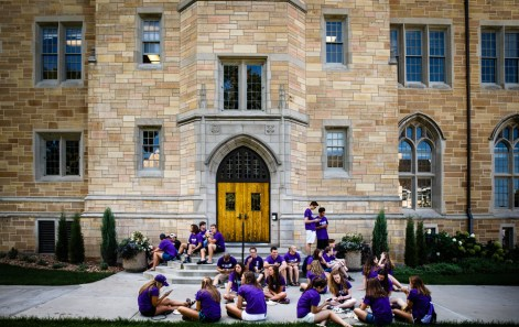 Students eat their food in front of Aquinas Hall during the Opening Celebration picnic.