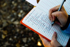 A student takes notes in a log book.