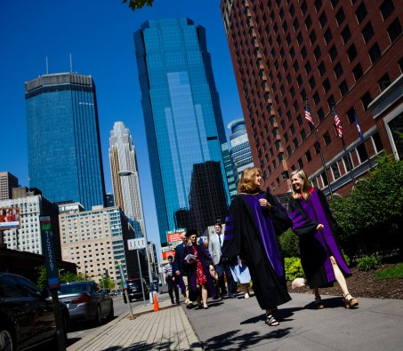 A new School of Law graduate (right) walks away from the Minneapolis Hilton with professor Julie Oseid following the School of Law Commencement ceremony May 13, 2017.