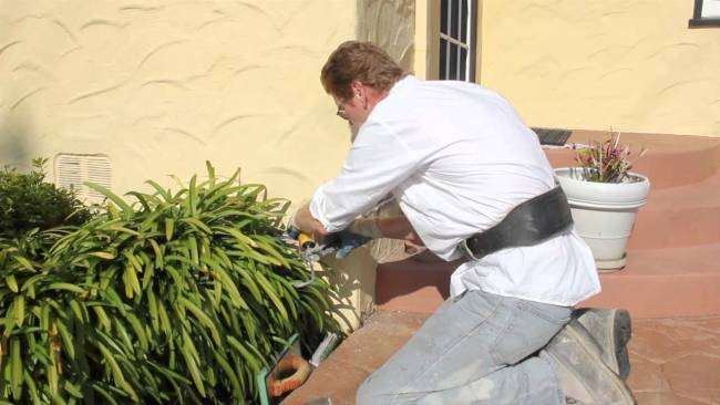 Repair large stucco cracks with strong caulking and stucco finish
