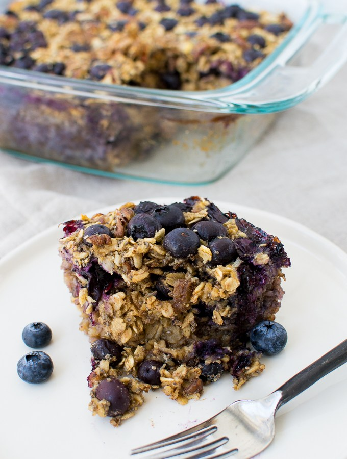 baked oatmeal recipe on a plate with blueberries