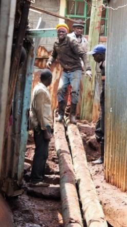 Men building abridge on muddy path