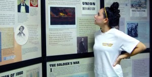 """Sophomore Kendra Mitchell reads over the """"Defining Liberty"""" exhibit displayed on the first floor of the Cook Library. Susan Broadbridge/Printz"""