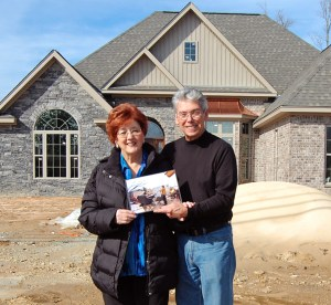 Willie and Carol Pierce hold a picture of their damaged house from the tornado's path of destruction last year. They now stand in front of their new home that is almost finished a year after the tornado. Susan Broadbridge/Printz