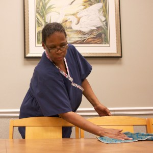 Linda Kyes wipes the table in one of the meeting rooms in McCarty Hall. Hunt Mercier/Printz