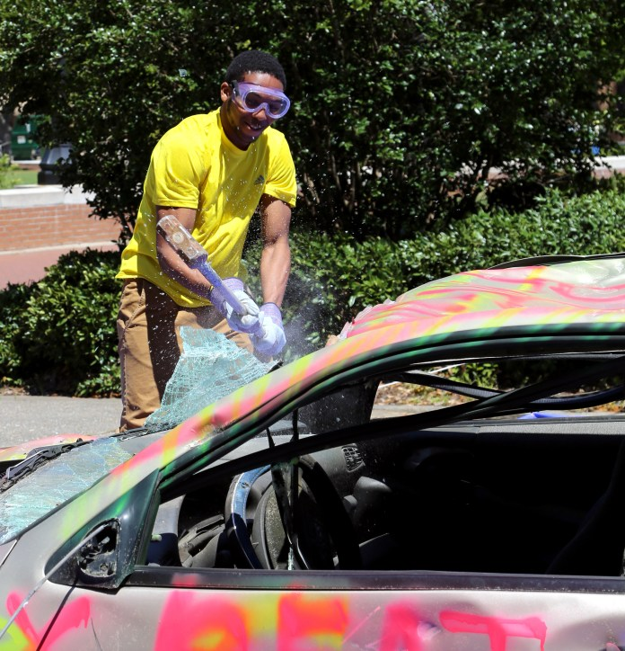 Junior Tae Smith participates in the Residence Hall Association's car smash on Wednesday, afternoon, April 16 on Centennial Lawn. Participants paid $1 for three hits on the car, and the proceeds went to  Relay for Life. Jessica King/Printz