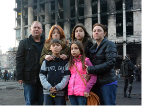 David Bundy and his family stand in front of the burned__- Trade Union in Independence Square in Kiev.   Photo by David Bundy
