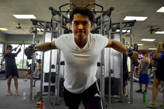 Junior Ryan Vo pumps out his last few reps at the Payne Center as he works on his gym etiquette Tuesday afternoon. | Photo by Aaron J. Stewart