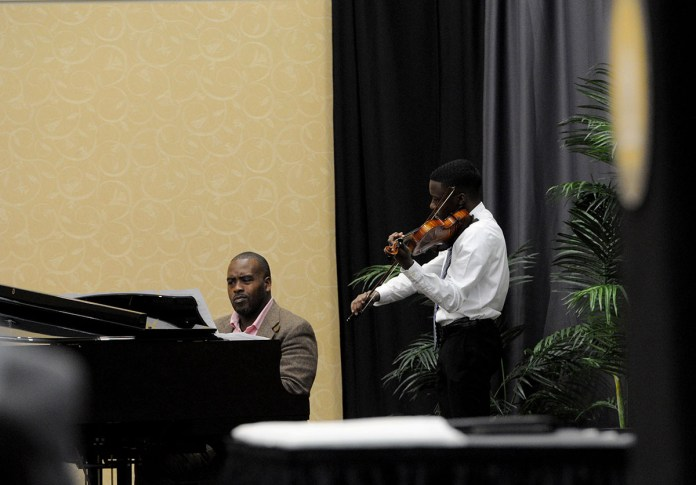 Pianist Tito Lanier and violinist John Uzodinma perform during the 9th Annual Dr. Martin Luther King Jr. Interracial and Ecumenical Prayer Breakfast held in the Thad Cochran Center in Hattiesburg, MS. Monday, Jan. 19, 2015.