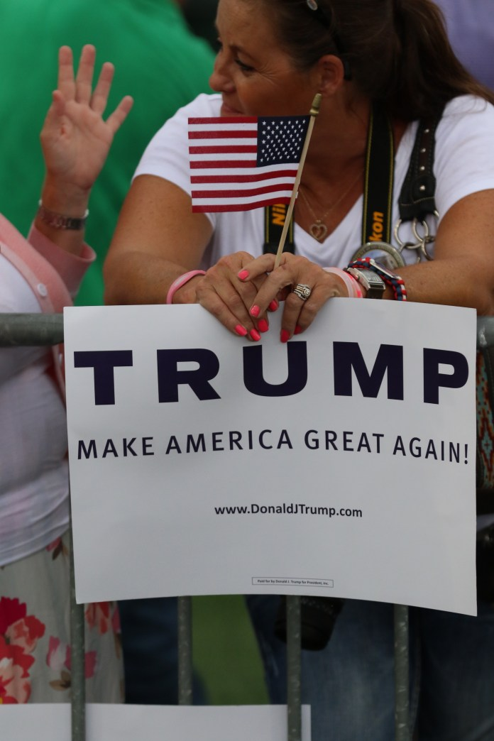 A member of the audience holding one of Trump's campaign signs and a miniature American Flag at Ladd-Peebles Stadium August 21, 2015