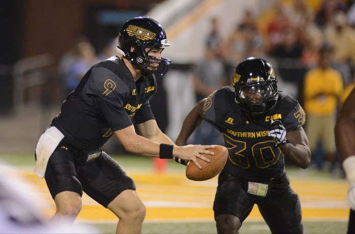 Southern Miss quarterback Nick Mullens prepares to make a hand-off to running back Jalen Richard during the game played against Mississippi in Hattiesburg on Saturday night.  Mary Alice Weeks/Student Printz