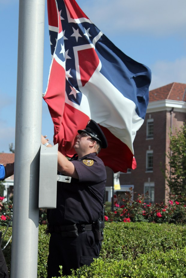 A university police officer takes down the Mississippi state flag on the Southern Miss campus this morning. Brittany Stewart/Student Printz