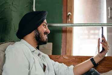 young man in turban communicating via video call on mobile