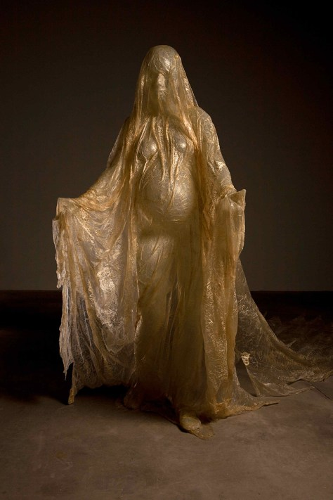 """""""Cette sculpture représente la Vierge enceinte de Jésus, debout les bras ouverts, figure de l'iconographie chrétienne rarement traitée. La Vierge est vêtue d'une tunique qui, tel un drapé mouillé, colle au corps, révélant avec impudeur sa nudité. Un voile, fabriqué à partir de boyaux de porc séchés, la recouvre de la tête aux pieds. La Vierge, paradigme d'une maternité sans tâche, devient ici une figure fantasmagorique, inquiétante, dans laquelle s'opposent, comme souvent dans les œuvres de Javier Pérez, les notions antagonistes du charnel et du spirituel, du laid et du beau, de l'impur et du sacré."""" (Source)  Javier Pérez Virgo Mater, 2012, Résine et boyaux de porc séchés"""