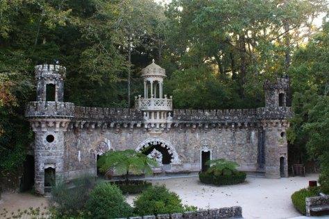 Le portail des Gardiens, dans le jardin du Palais, est l'une des Folies du domaine. Elle donne sur l'entrée d'une grotte conduisant au Puit Initiatique.